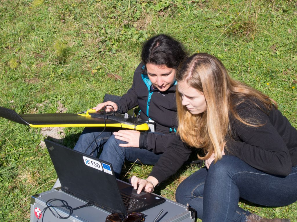 CartONG staff looking at data that has just been collected by FSD's eBee drone. Photo: Timo Lüge